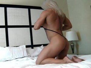 Wanita cantik berotot di tempat tidur, wanita cantik berotot dalam pakaian seksi memamerkan tubuh kuat yang dia pose di tempat tidur. Softcore solo.